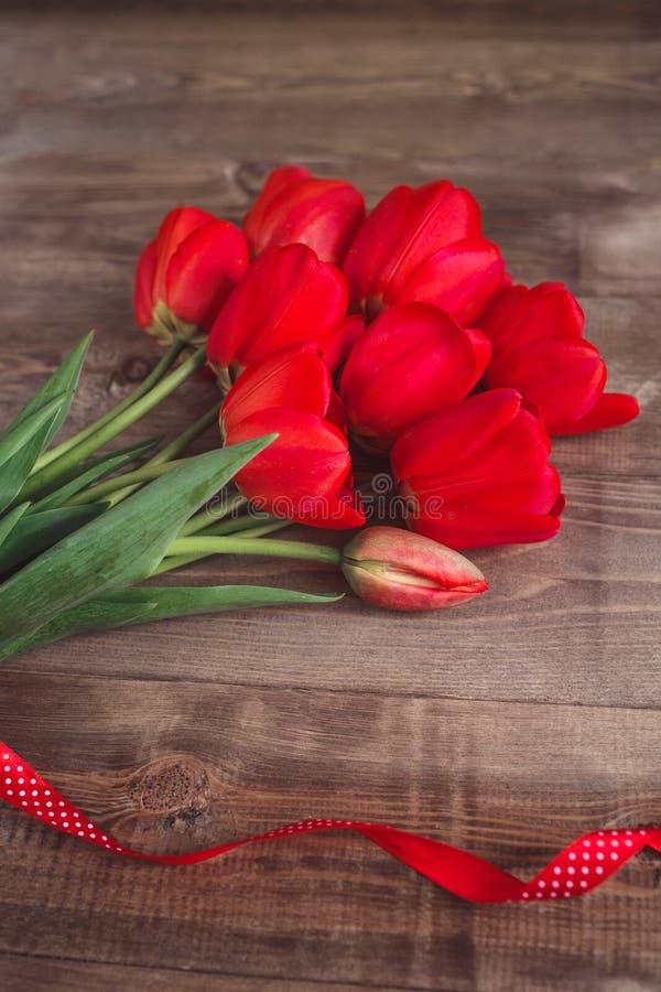 Juste plu en fonction Bouquet des tulipes rouges sur le fond en bois brun Enfantez le fond de jour du ` s et de jour de valentine photos stock