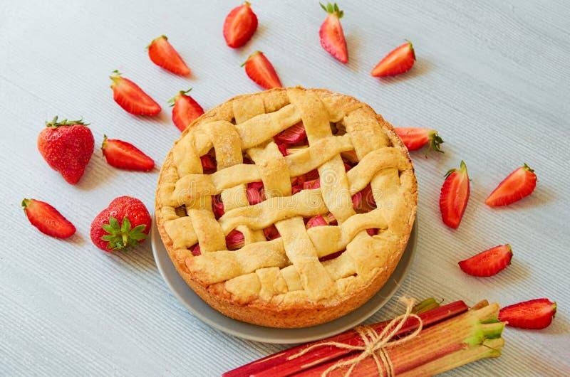 Juste tarte cuit au four de fraise de rhubarbe sur le fond gris de cuisine Tarte de baies de Veggie décorée des fraises fraîches  photo stock