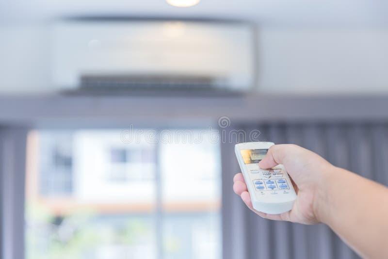 Justera AC-temperaturen med fjärrkontroll till att betinga för väggtypluft royaltyfri bild