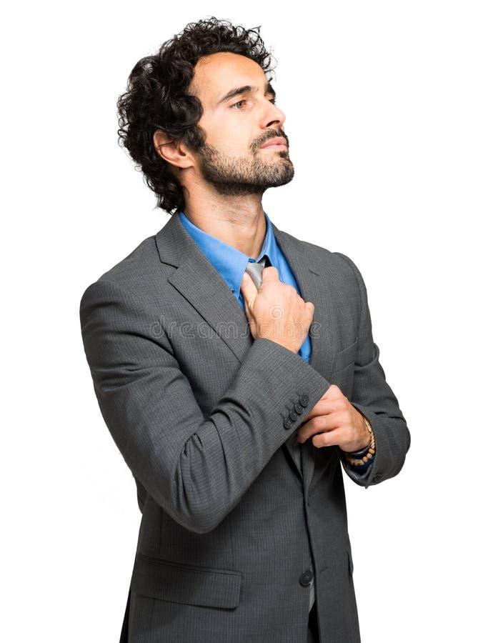 justera den stiliga affärsmannen hans tie royaltyfri foto