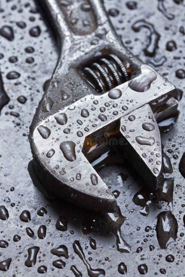 Justerbar skiftnyckel i vattendroppar royaltyfria bilder
