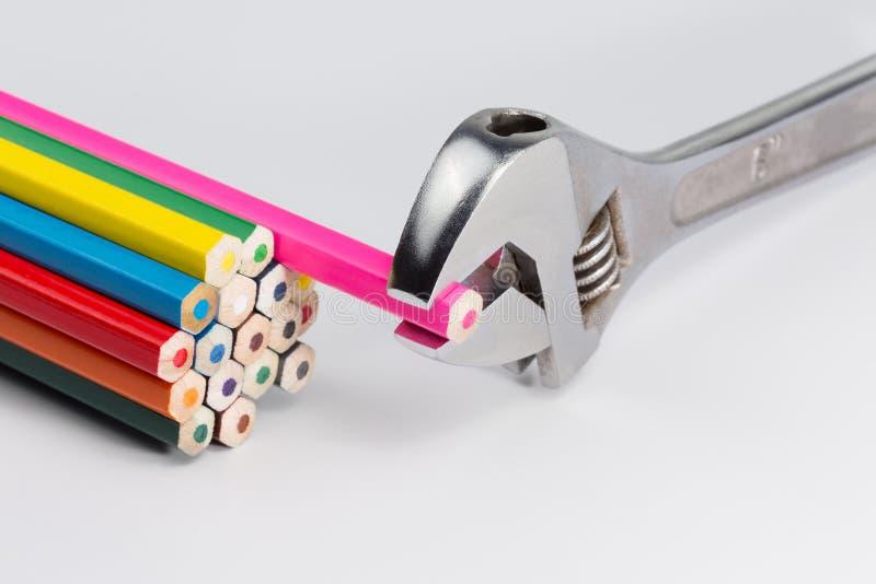 Justerbar skiftnyckel och färgade blyertspennor arkivfoto