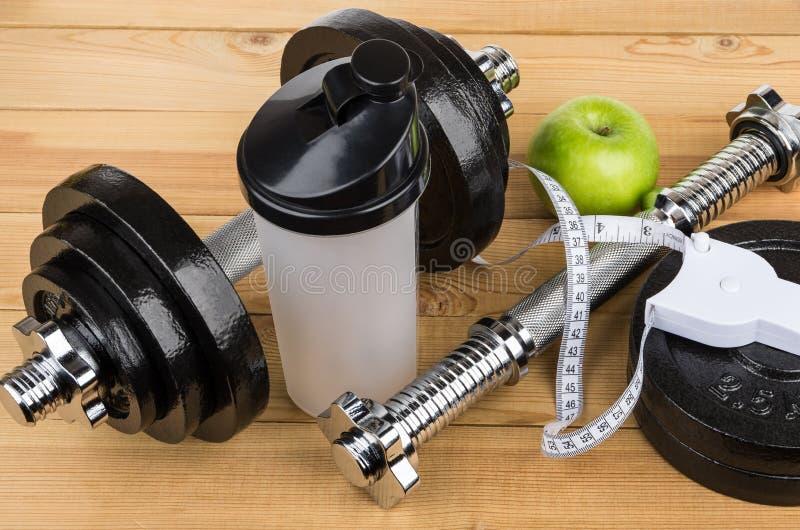 Justerbara hantlar, plast- shaker, äpple och måttband arkivfoto