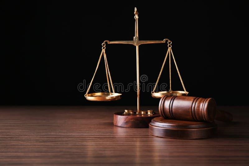 Justiça escala e julga o martelo na tabela contra o fundo preto fotografia de stock