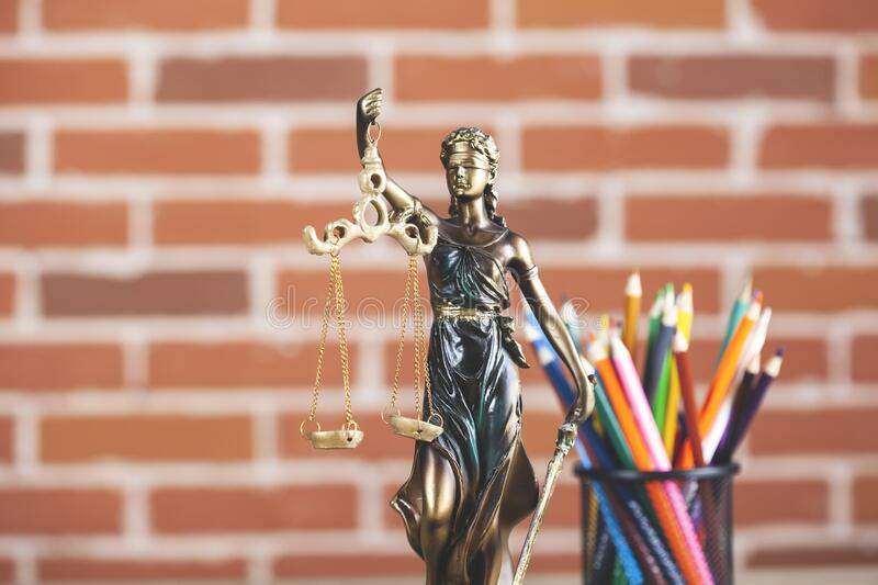 Justice lady on table. On brick wall background stock image