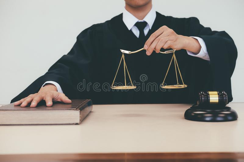 Justice and law concept. Male lawyer in the office with brass scale royalty free stock image