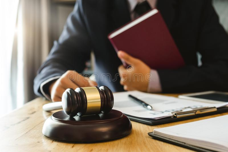 Justice and law concept.Male judge in a courtroom with the gavel,working with,digital tablet stock photos
