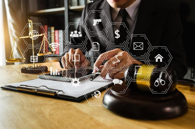 Male lawyer in the office with brass scale. Justice and law concept.Male judge in a courtroom the gavel, working with smart phone and laptop and digital tablet stock images
