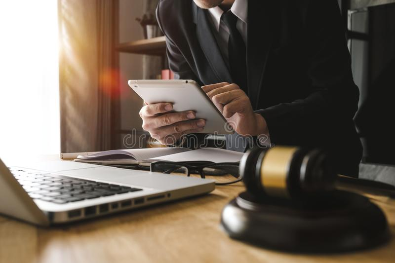 Male lawyer in the office with brass scale on wooden table. justice and law concept in morning light royalty free stock images