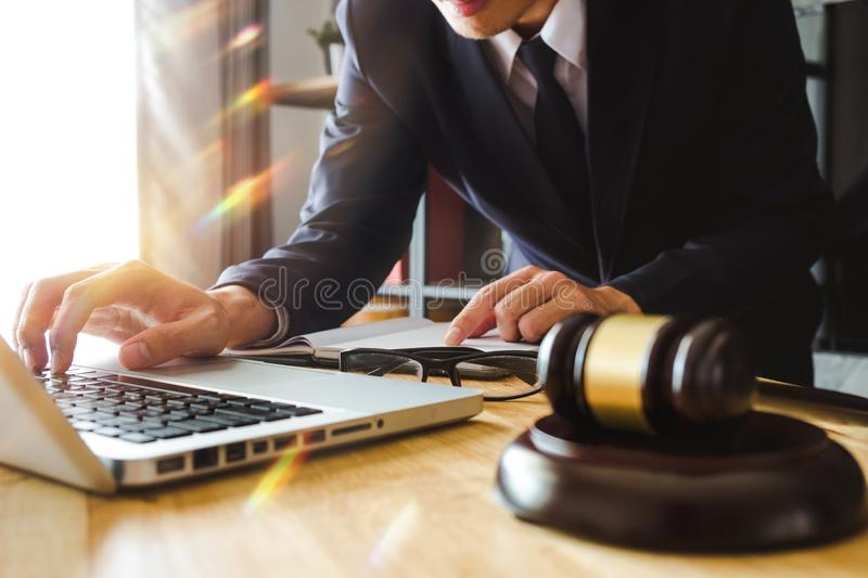 Male lawyer in the office with brass scale on wooden table. justice and law concept in morning light royalty free stock photos