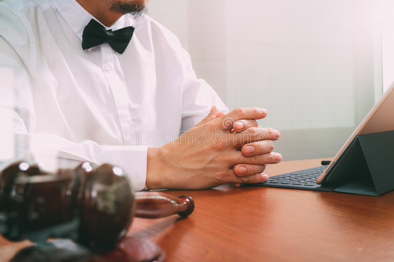 Justice and Law context.Male lawyer hand working with smart phone,digital tablet computer docking keyboard with gavel and. Document on wood table royalty free stock photography