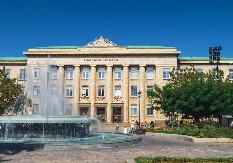Justice palace in Ruse, Bulgaria. Ruse, Bulgaria - September 10, 2017: View of Justice palace with fountain and walking people, Ruse, Bulgaria royalty free stock photo