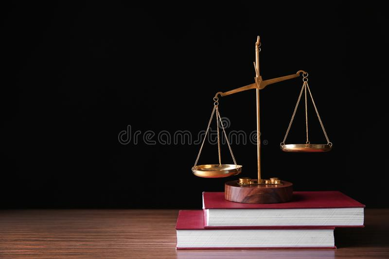 Justice scales and books on table against black background royalty free stock photo