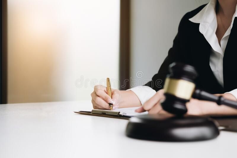 Justice scales, justice hammer and Litigation and Litigation document, female lawyer using pen point law book, working legal law. At lawyer office royalty free stock photo