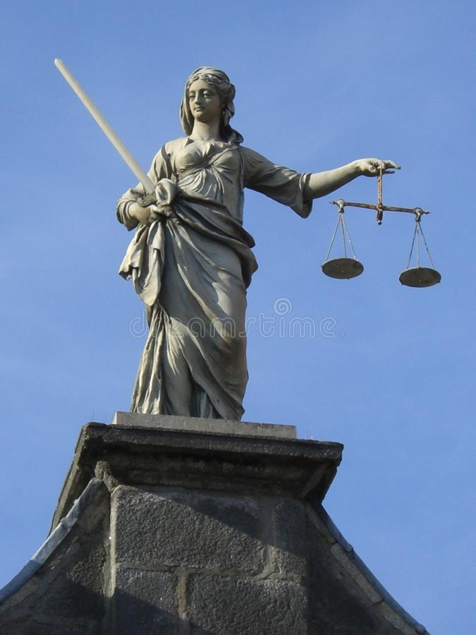 Justice Statue. Justice Lady Stone Statue not blind on the top of a building holding a scales and a sword royalty free stock photo