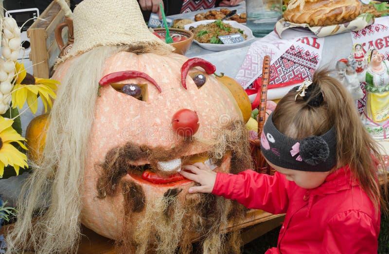 justo Halloween A menina examina e toca na abóbora vestida acima como da cabeça de um homem imagem de stock royalty free