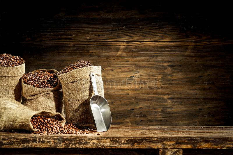 Jute sacks with fresh coffee beans on wooden board background. Jute sacks with coffee beans on wooden board background and some empty space for text or stock photo