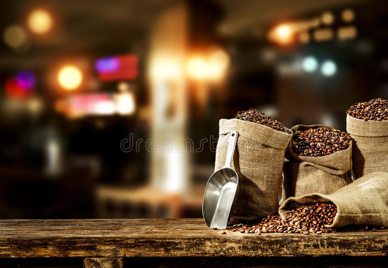 Jute sacks with fresh coffee beans on wooden board with blurred restaurant background. Jute sacks with coffee beans on wooden board with blurred restaurant royalty free stock photos