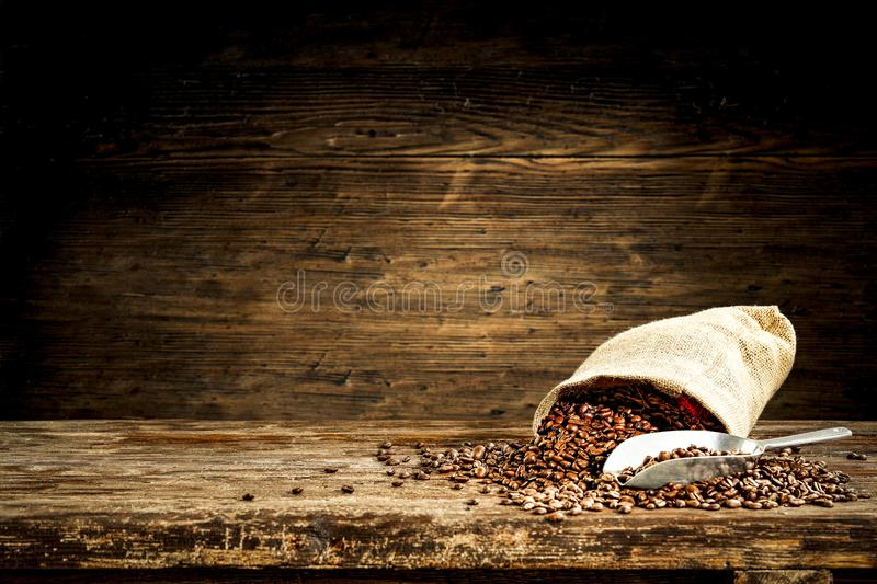 Jute sacks with fresh coffee beans on wooden board with blurred restaurant background. Jute sacks with coffee beans on wooden board with blurred restaurant royalty free stock photo