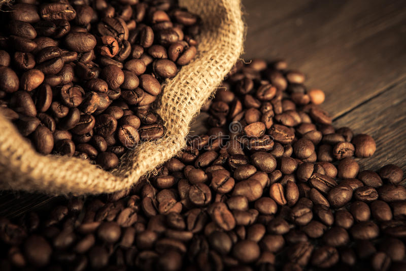 Jutepåse med kaffebönor arkivbilder