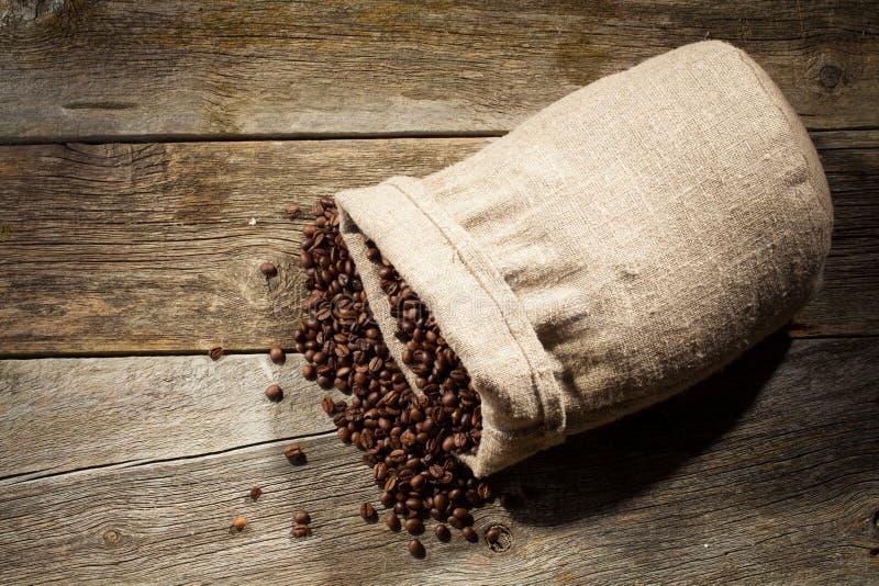Jutezak van koffiebonen tegen donkere houten achtergrond royalty-vrije stock afbeelding