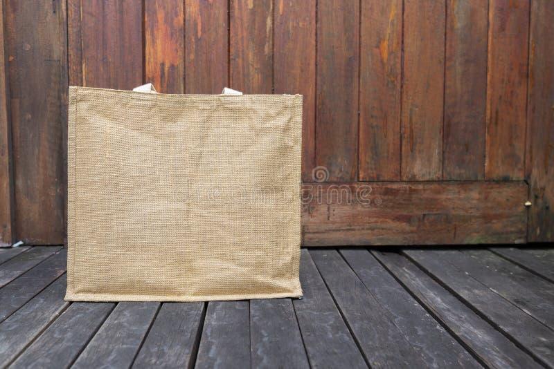 Jutowa torba na drewnianej podłoga z przestrzenią na drewnianym tle fotografia stock