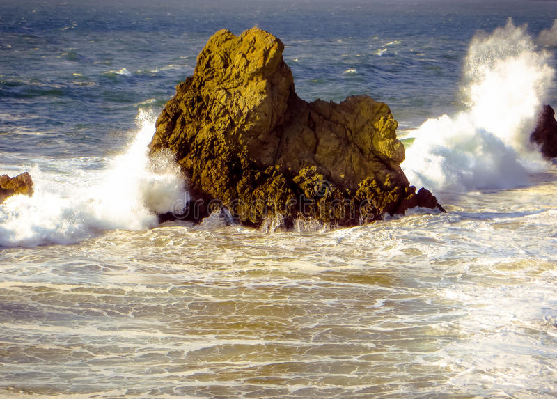 Jutting rock with crashing waves royalty free stock photos