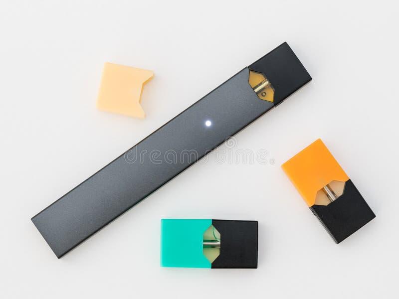 JUULpods ed erogatore che contengono i sapori differenti di nicotina fotografie stock