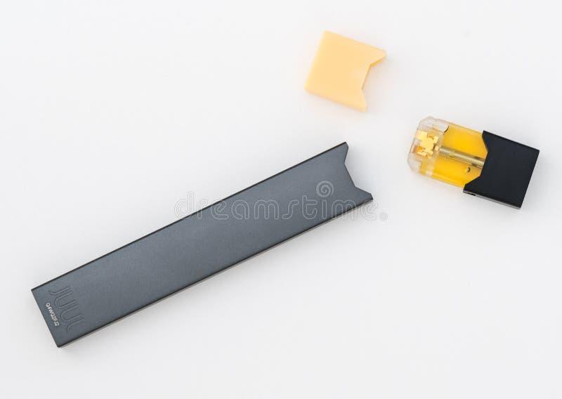 JUULpods ed erogatore che contengono i sapori differenti di nicotina fotografia stock