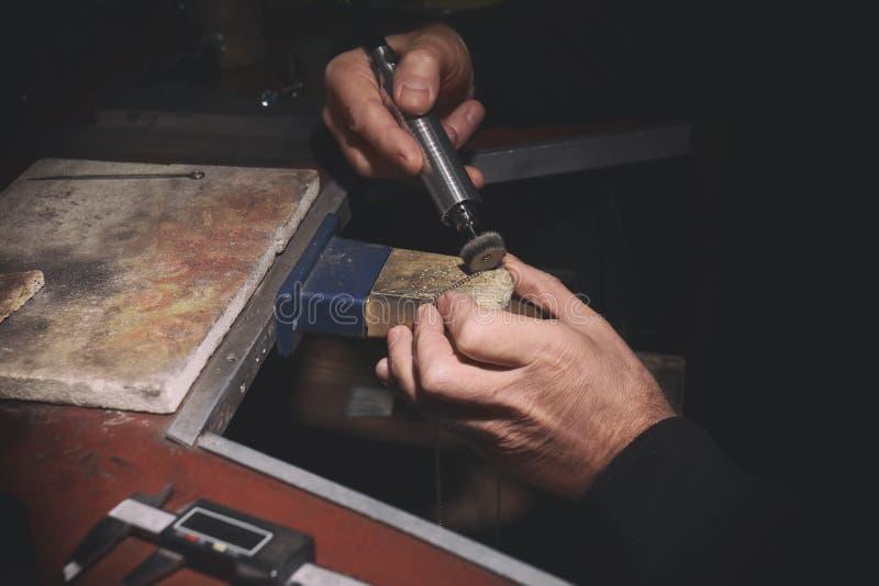 Juvelerare som polerar den guld- kedjan med det roterande hjälpmedlet royaltyfri foto