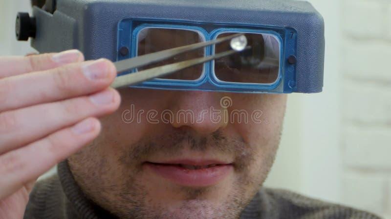 Juveleraren bär skyddsexponeringsglas som behas med kvalitet av ädelstenen arkivfoton