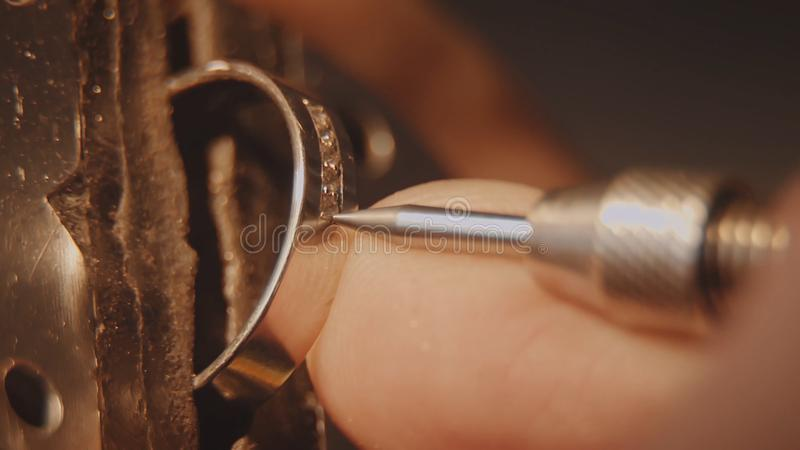 Juveleraren ställer in en ädelsten Hantverksmyckendanande Reparera för cirkel Sätta diamanten på cirkeln Makro royaltyfri foto