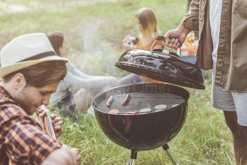 Juventud tranquila que arregla comida campestre en naturaleza foto de archivo libre de regalías