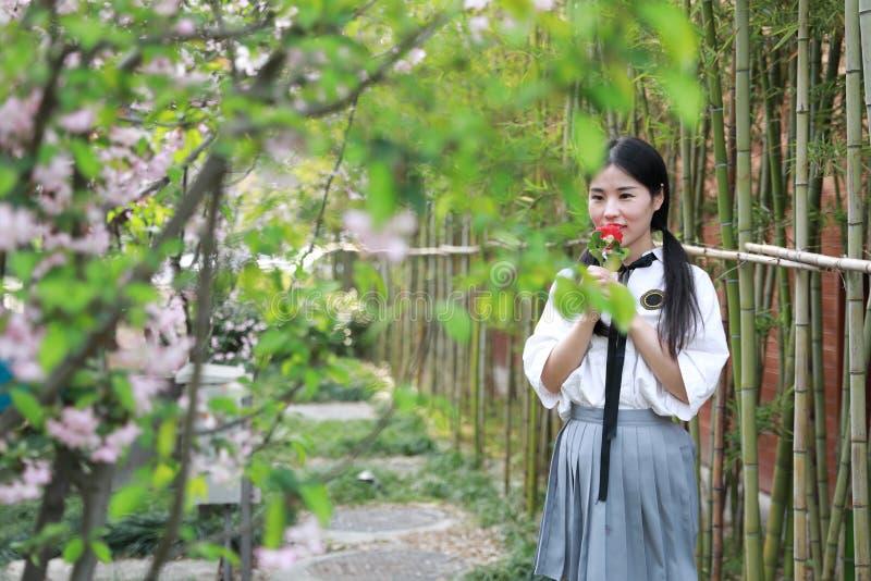 A juventude bonita adorável bonito nova feliz chinesa asiática do estudante em um jardim do parque exterior no cheiro do verão au imagem de stock royalty free
