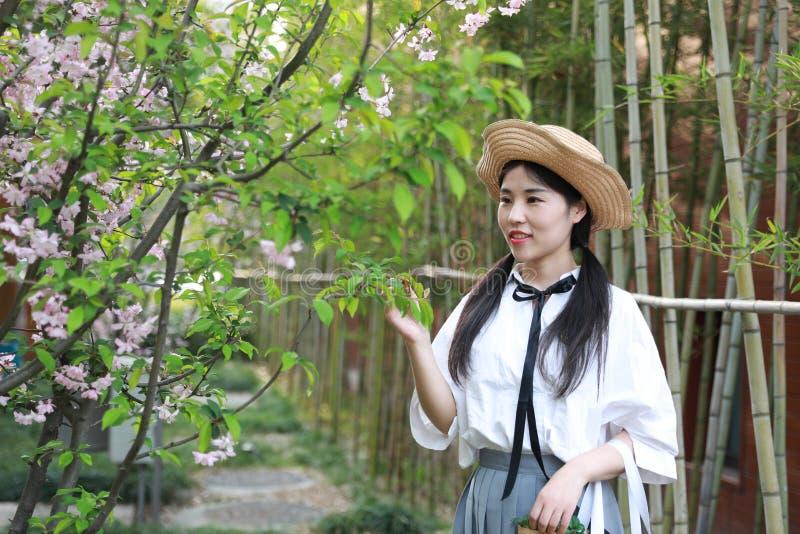 Juventude bonita adorável bonito nova feliz chinesa asiática do estudante em um jardim do parque exterior no verão imagens de stock royalty free