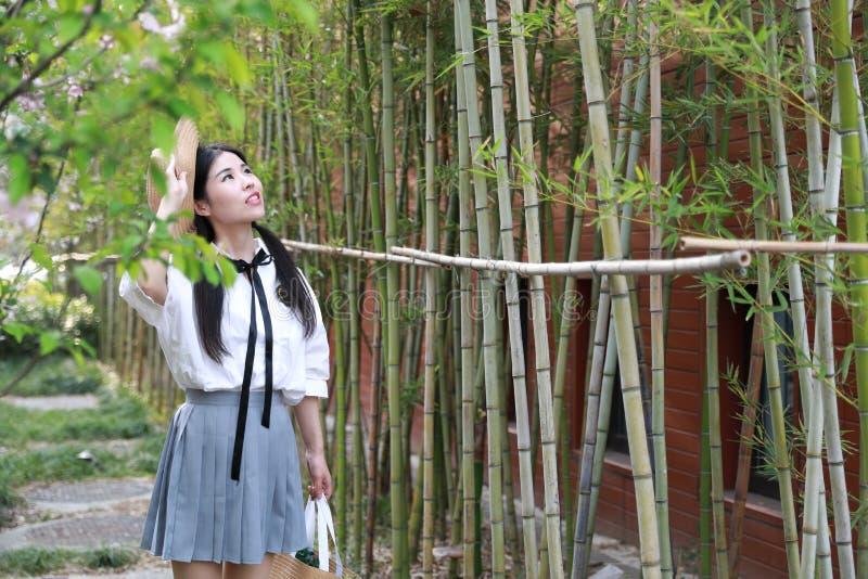 Juventude bonita adorável bonito nova feliz chinesa asiática do estudante em um jardim do parque exterior no verão fotos de stock royalty free