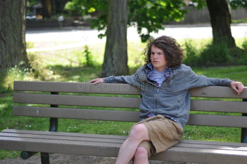 A juventude desabrigada senta-se no banco fotos de stock