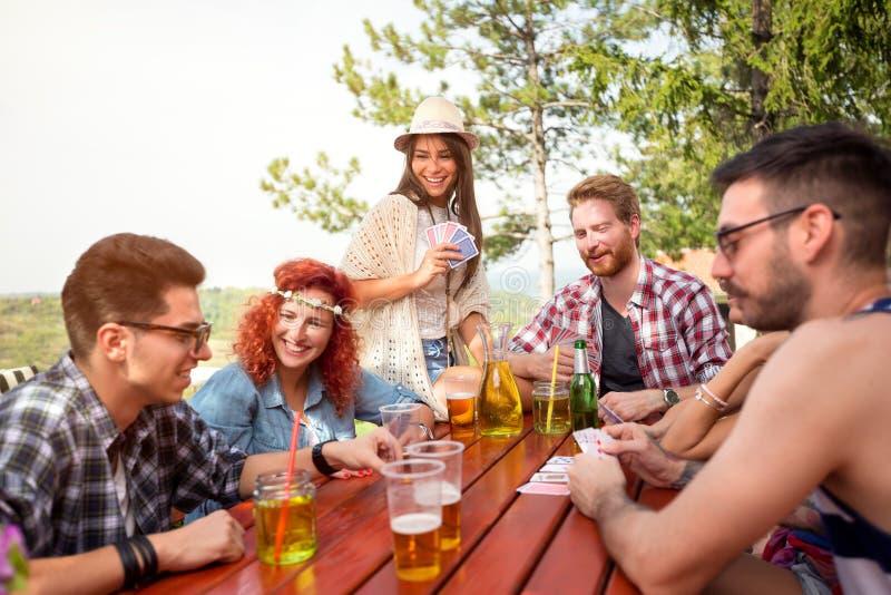 Juventude que aprecia com amigos e jogo de cartas na floresta fotos de stock royalty free