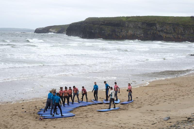 Juventude que está sendo ensinada surfar na praia do ballybunion fotografia de stock