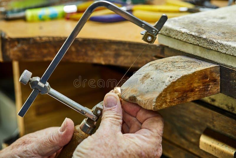 Juwelenproductie Juwelier gebruikend zaag om juwelen tot stand te brengen stock fotografie