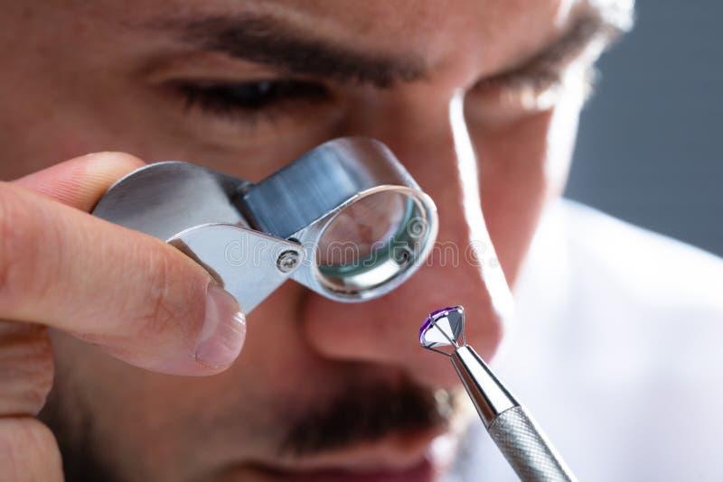 Juwelier Looking At Diamond Through Magnifying Loupe stock afbeeldingen