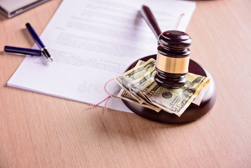 Juzgue el mazo y el dinero al lado del juicio en la tabla de madera imágenes de archivo libres de regalías