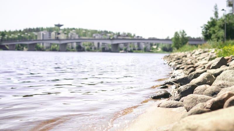 Jyvaskyla, Finland. Lake and the bridge of Kuokkala. Waves hitting rocks. Beautiful Finnish nature. Sunny summer landscape. royalty free stock image