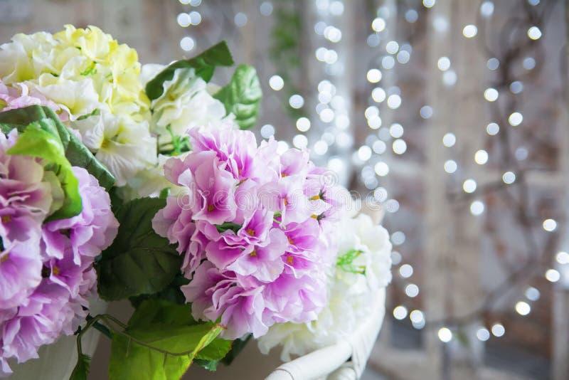 Künstliches Rosa und gelbe Blumen auf bokeh Hintergrund stockfotografie