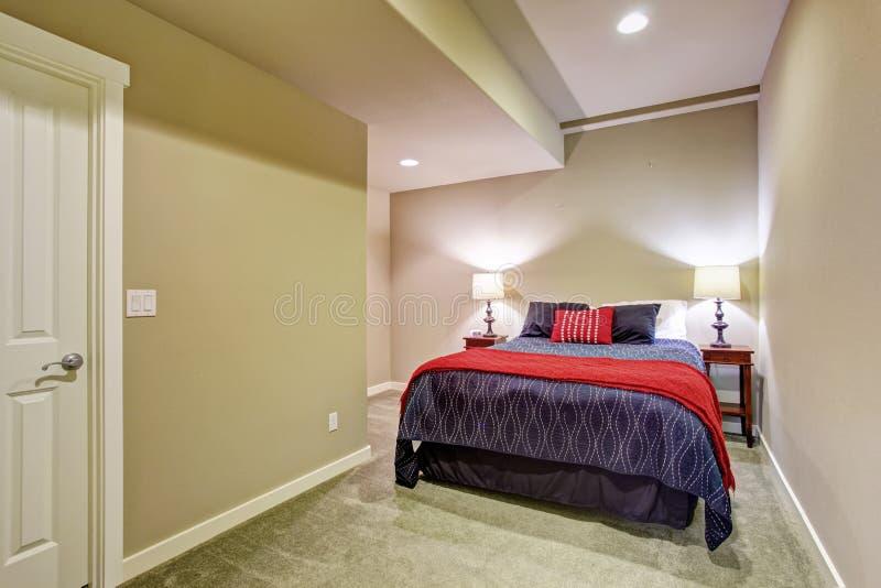 Källaregästsovrum med blå och röd säng arkivbilder