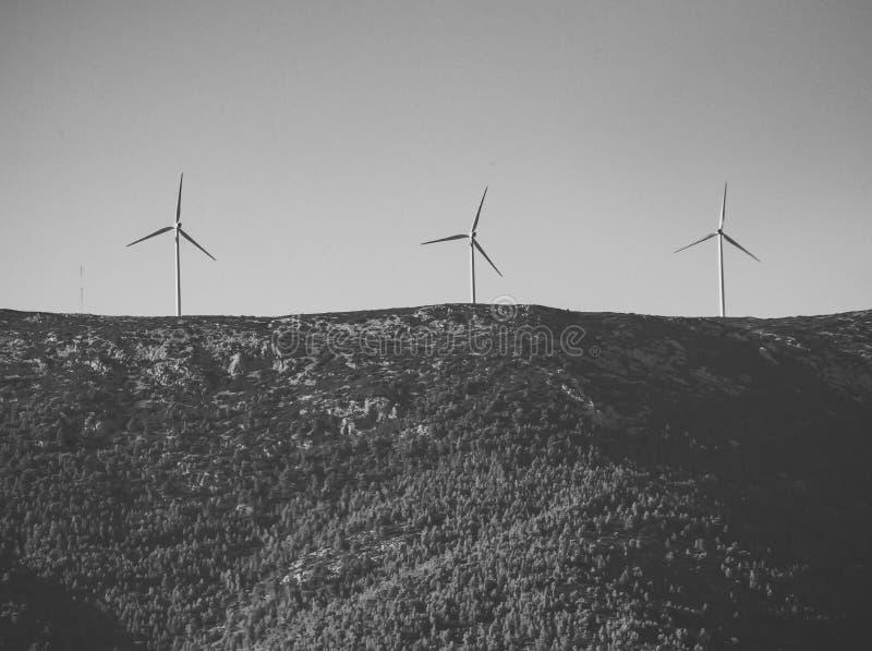 Källbegrepp för alternativ energi Jätte- vita väderkvarnar på berg Väderkvarnar vindgeneratorer på kullen, berg royaltyfria bilder