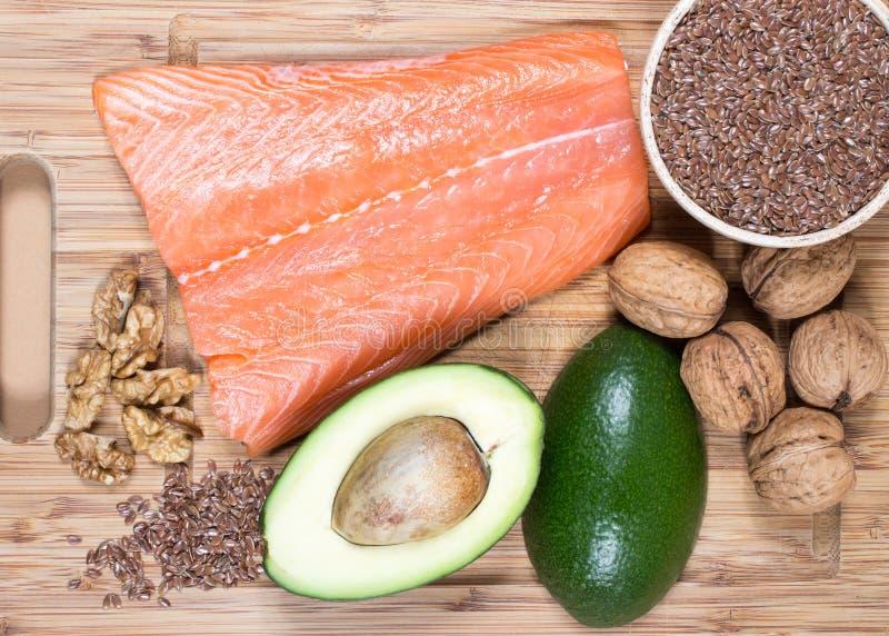 Källor av omegan 3 fettsyror: flaxseeds, avokado, lax och valnötter arkivfoto
