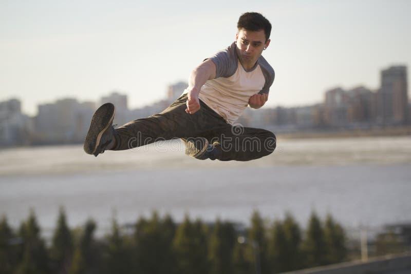 Kämpen för den unga mannen utför flygspark framme av horisont arkivfoto