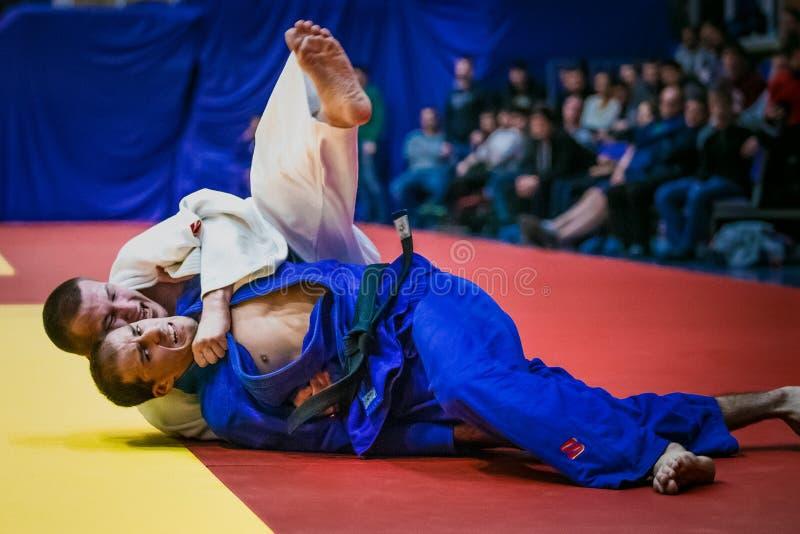 Kämpfen Sie auf tatami zwei Athletenringkämpfer in den Schlüssen stockfoto