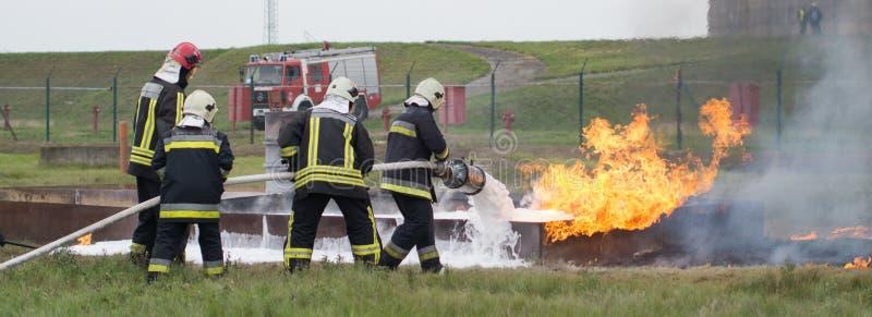 Kämpfendes Feuer mit einem Schaumfeuerlöscher lizenzfreie stockbilder
